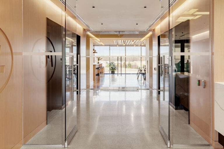 Glass doors to elevator bank in blond woods with pale flooring.
