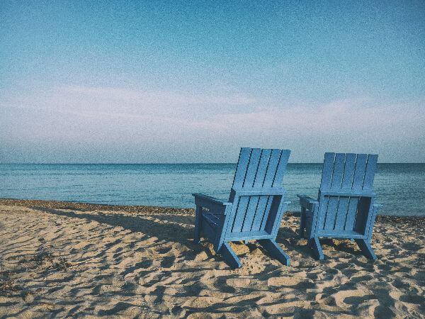 Two deck chairs on a beach