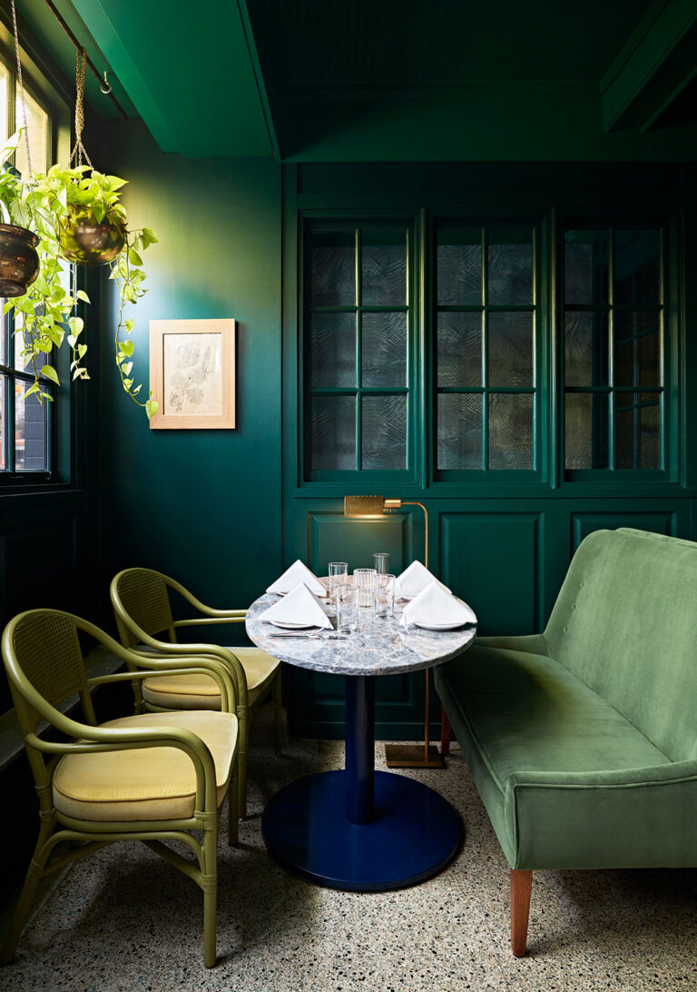 Table for four at La Banane with two pistachio green chairs opposite a green bench.