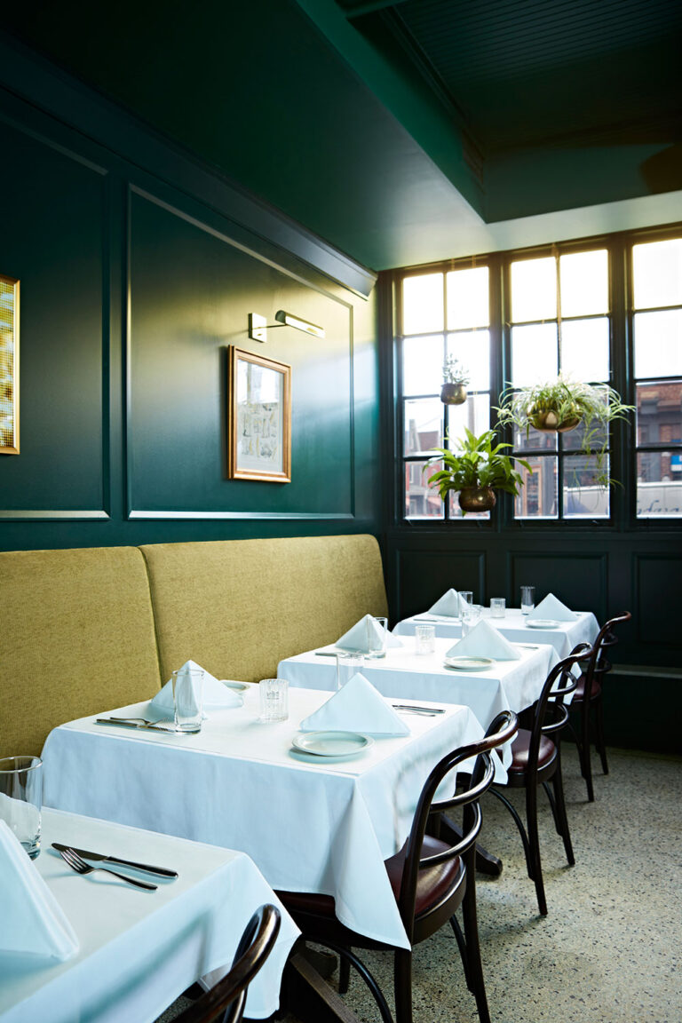 Emerald green dining area at La Banane with sage green seating.