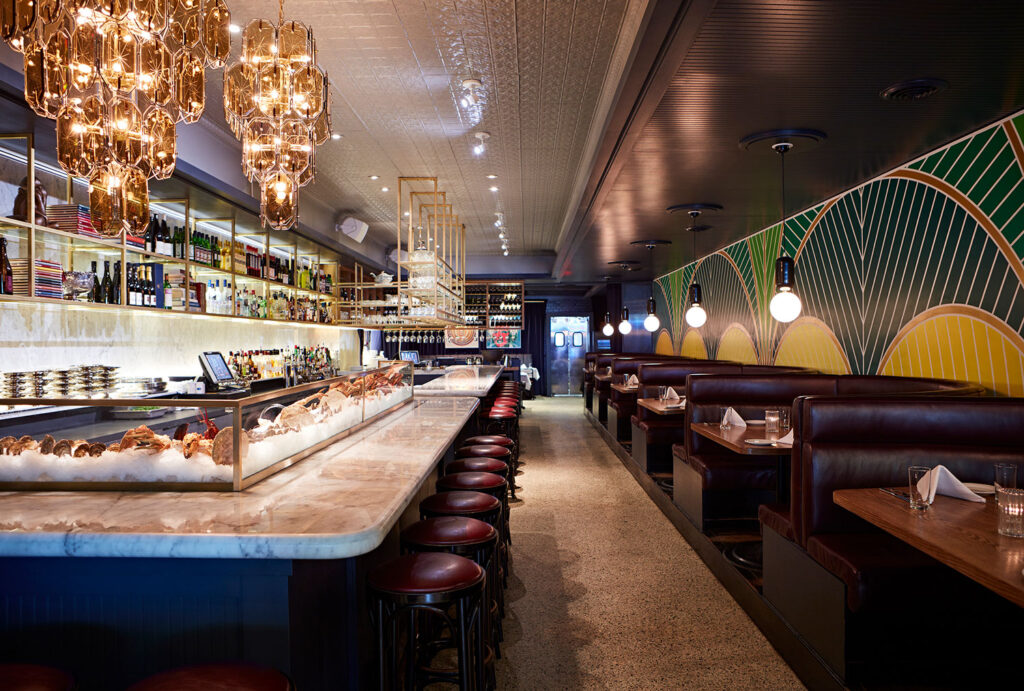 Bar and seafood area at La Banane with gold and glass chandelier, opposite leather banquettes and graphic, geometric mural.