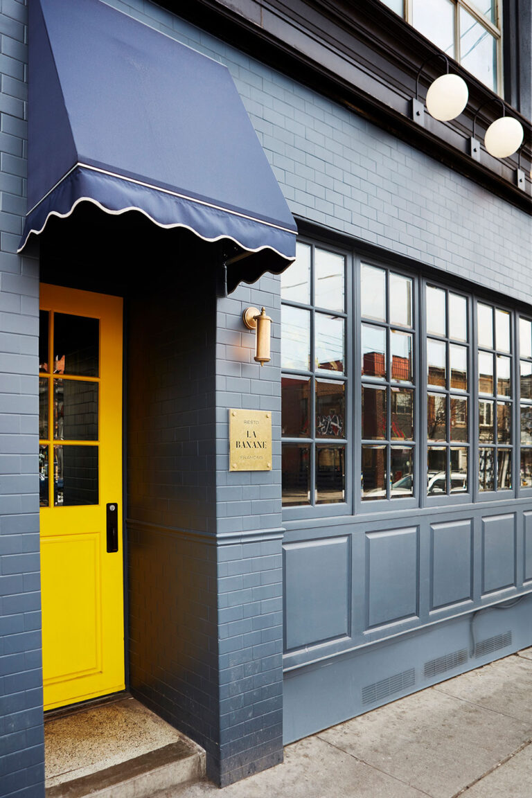 Exterior view of La Banane with a bright yellow door on a navy-teal facade.