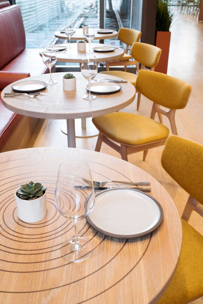Series of tables set for two at Clay Restaurant, the wood top of the table is engraved with concentric circles, and the chairs have yellow coverings.