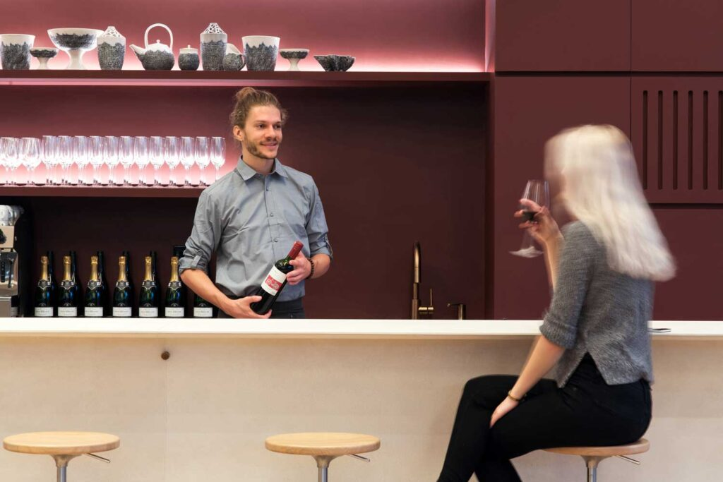 Man serving wine behing a modern looking bar