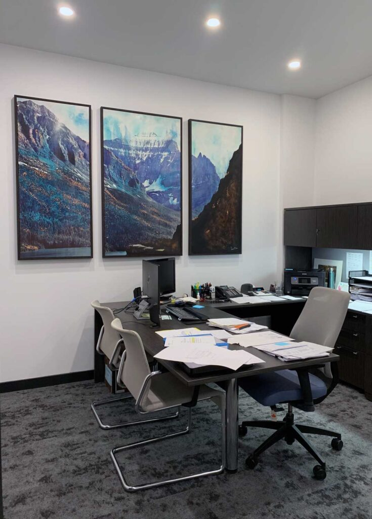 Office with white walls, and tryptych painting of mountains.