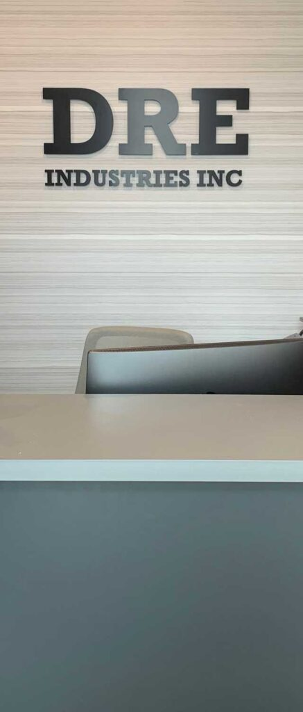 Reception desk with black feature that reads, 'DRE Industries'