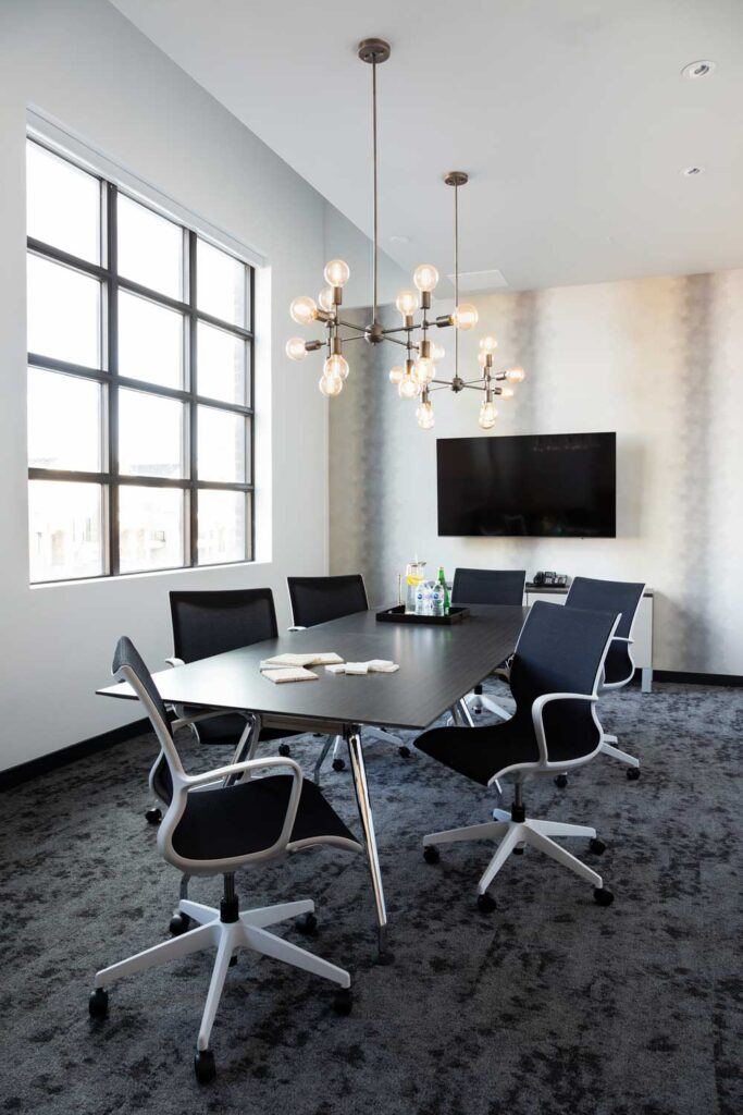 Small boardroom with white walls and dark modern table.