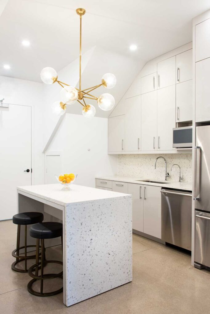 Bright office kitchen with gold light fixture