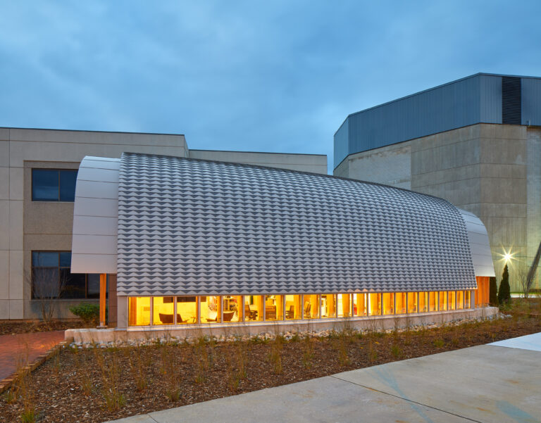 Exterior evening view of Odeyto Indigenous Centre, shows the shape of the building inspired by the forms of a canoe.
