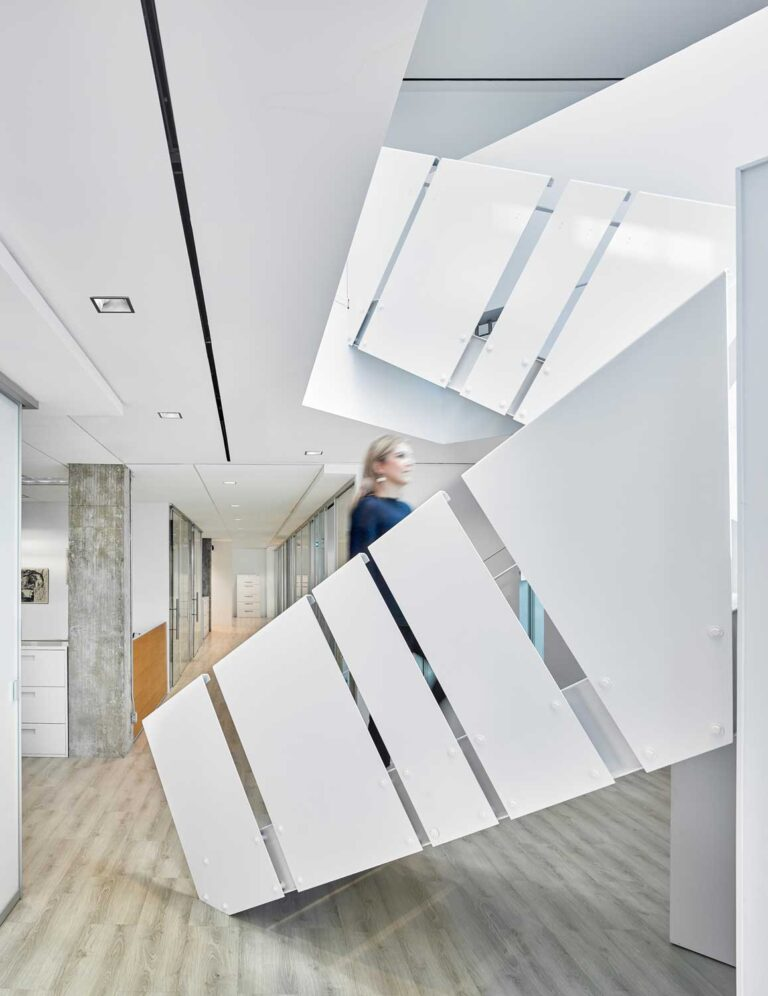woman walking up white staircase
