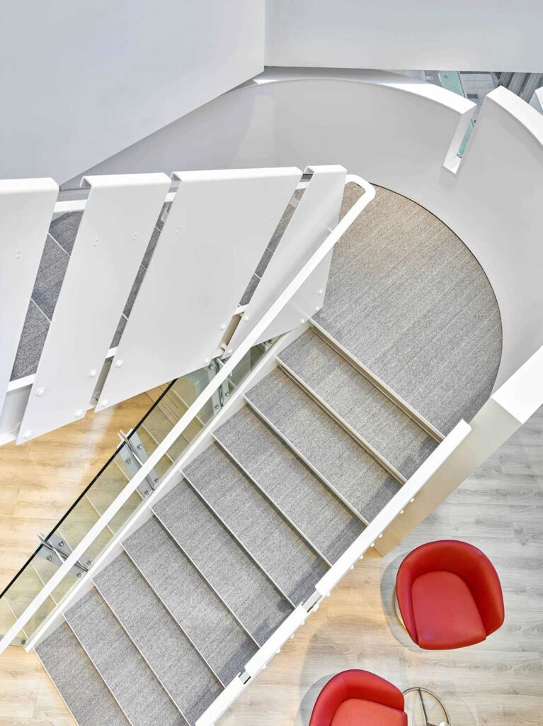 Bird's eye view of white staircase with gray carpeting