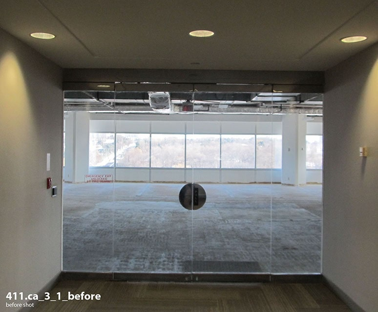 Raw office with concrete flooring, viewed through closed glass doors.