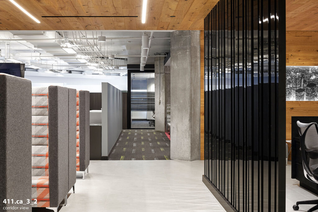 Office corridor with a sleek, black textured wall, with couches with red and gray.