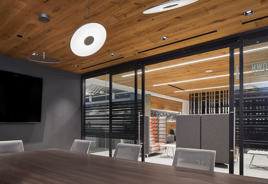 Meeting room with gray walls, and wood panelled ceiling.