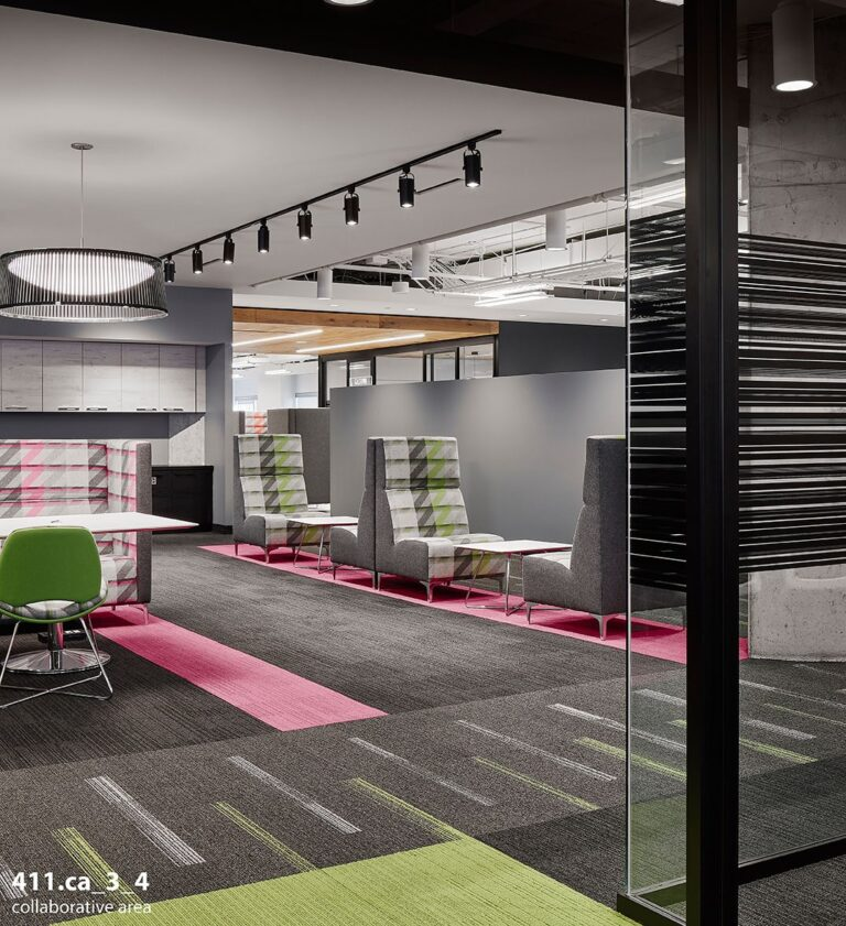 View from a glass walled meeting room to a series of meeting couches with a gray and lime green colour scheme.