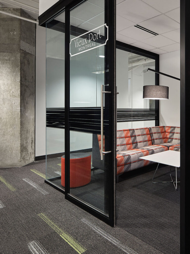 A small meeting room with a red and gray sofa named after the