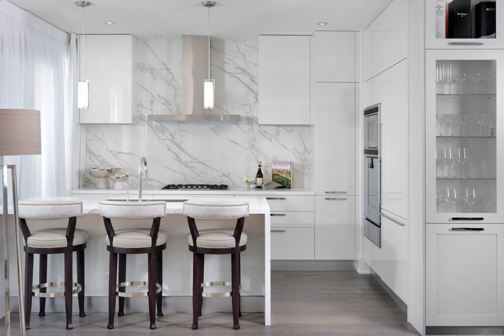 A kitchen done in white and pale gray marble, with a bar.