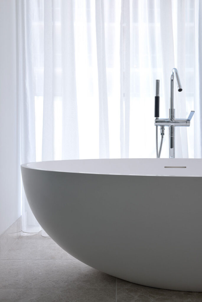 Close up of rounded freestanding bathtub.