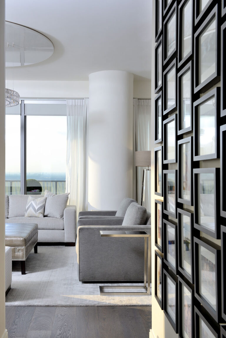 Entry way of a condo with a gallery wall of black picture frames on the right.