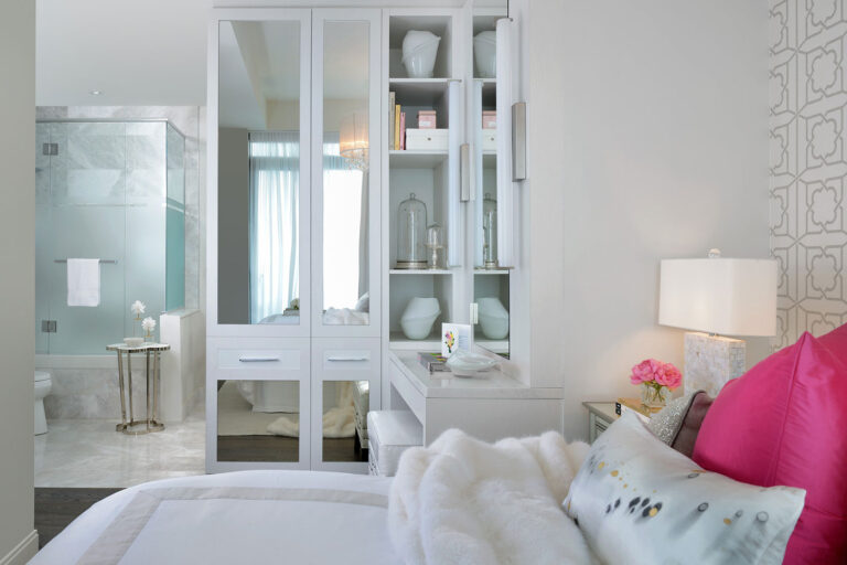 Double bed made with pale gray duvet. Mirrored cabinets opposite the bed reflect the window.