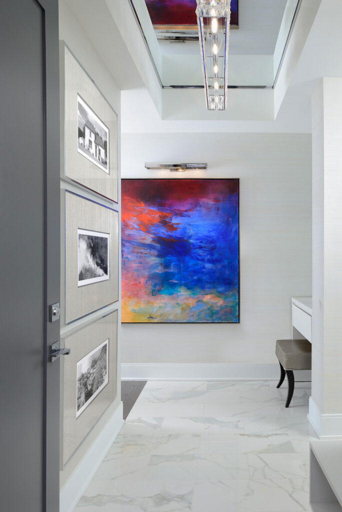 A bright abstract painting at the end of a hallway with gray carpeting and walls.