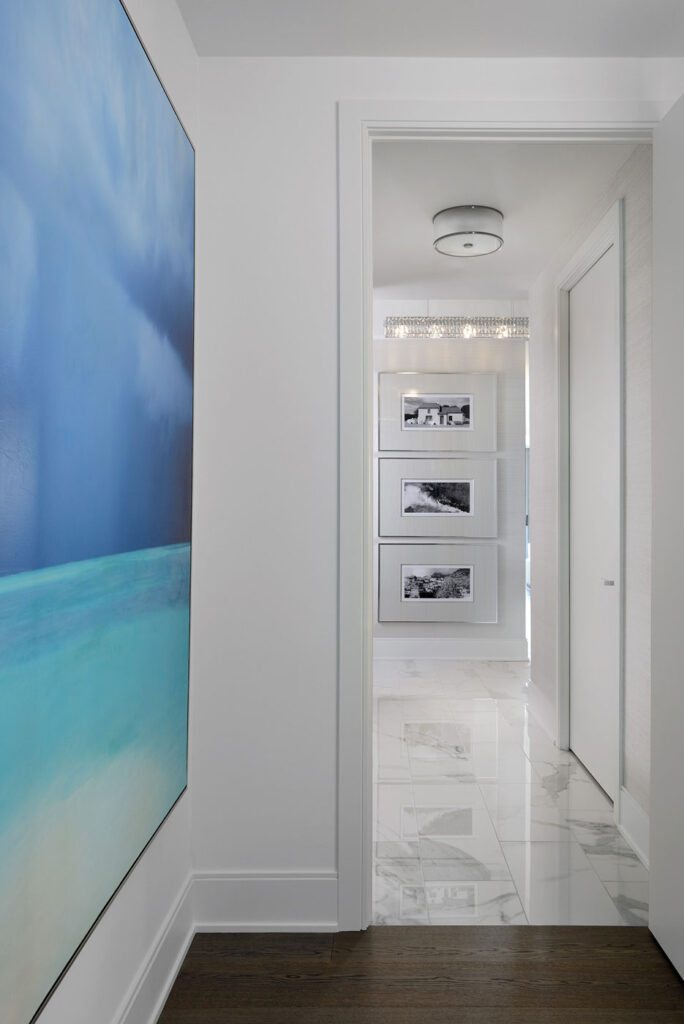 View down a hallway to three black and white pictures.