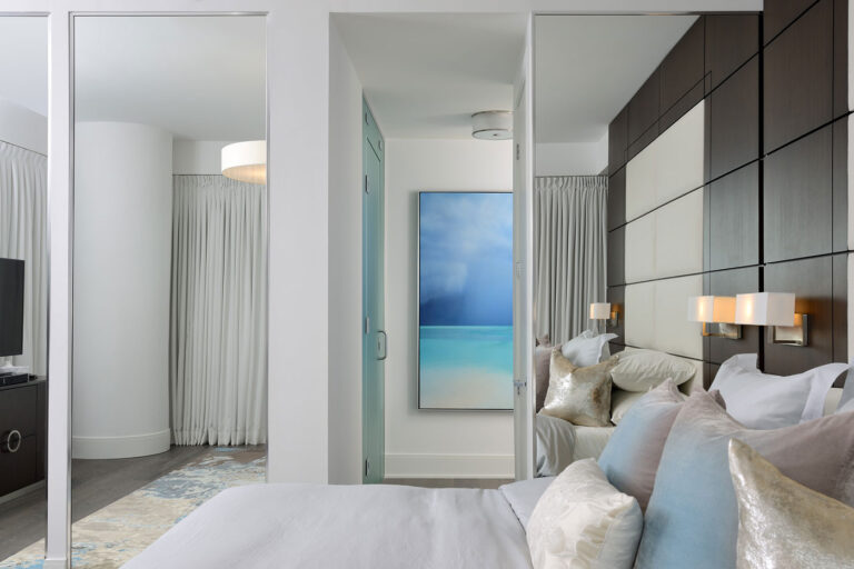 View across a bed made with gray linens to the hallway outside.