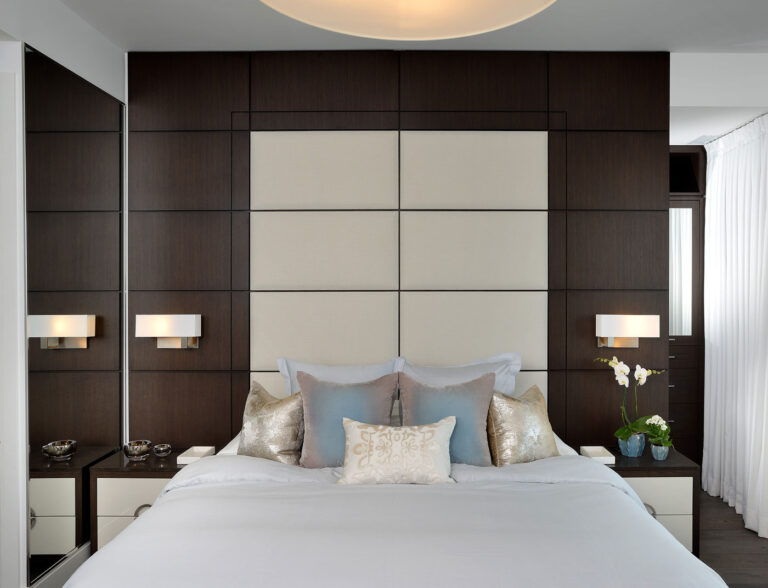Queen sized bed made in gray linens with a cream and wood panelled wall in behind.