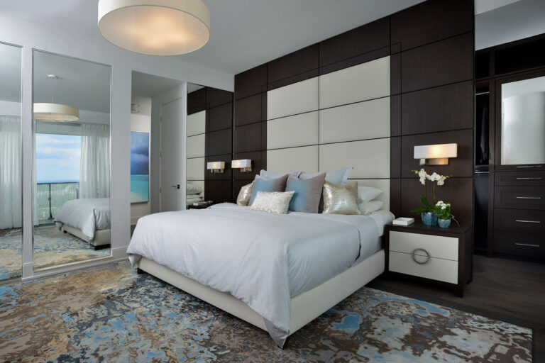 Bedroom with wood panelled wall and mirroed closets.