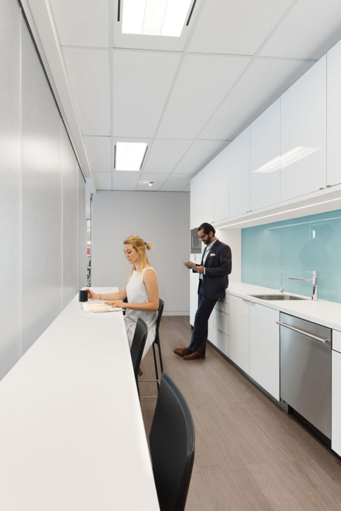 Two employees enjoy the break room with white cabinetry.
