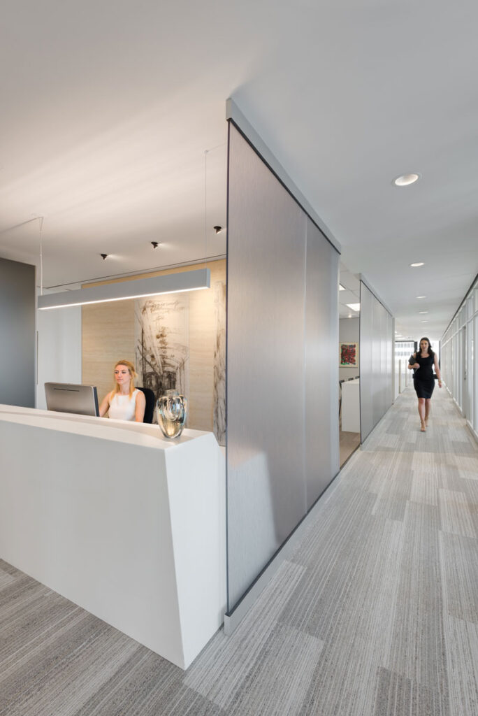 Modern office with gray flooring, and large white marble reception desk.