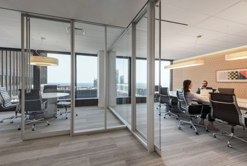 View of boardroom with glass walls and adjacent glass walled office