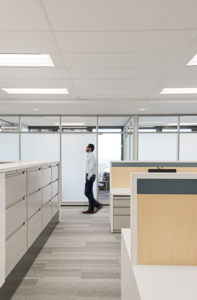 A man walks through the Jones Collombin office at the end of a hall of filing cabinets.