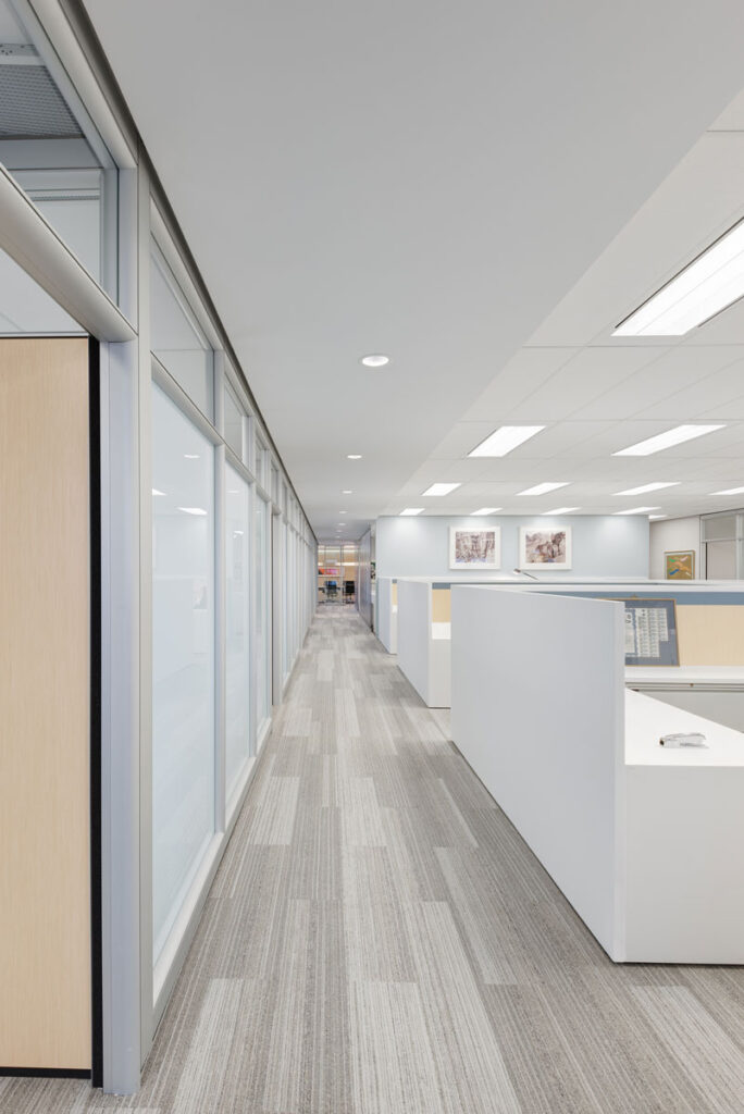 Long view of office space with white desks and cubicles on the right hand side.