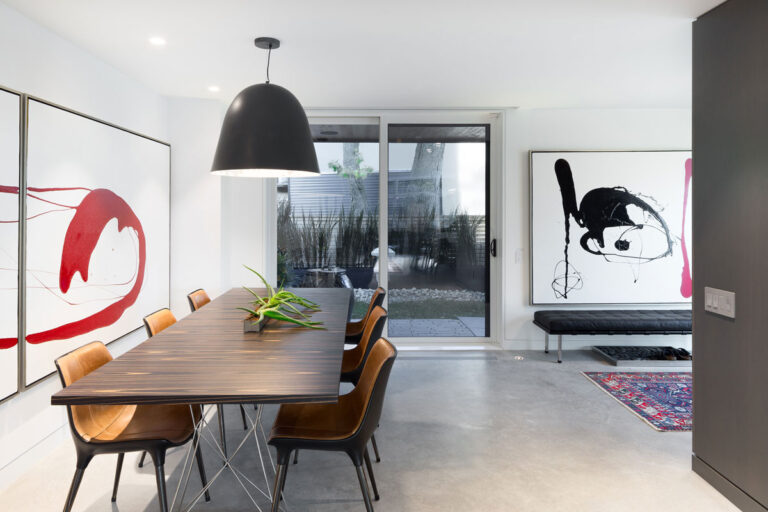 Living / dining room, with pale floors and modern art on the walls.