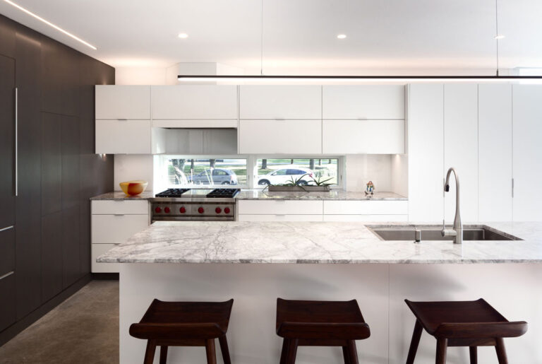 Modern white kitchen with rectuangular island topped with gray and white marble, and three black stools.