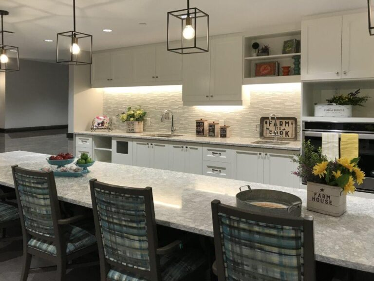 Kitchen area with white countertops and a long rectangular island.
