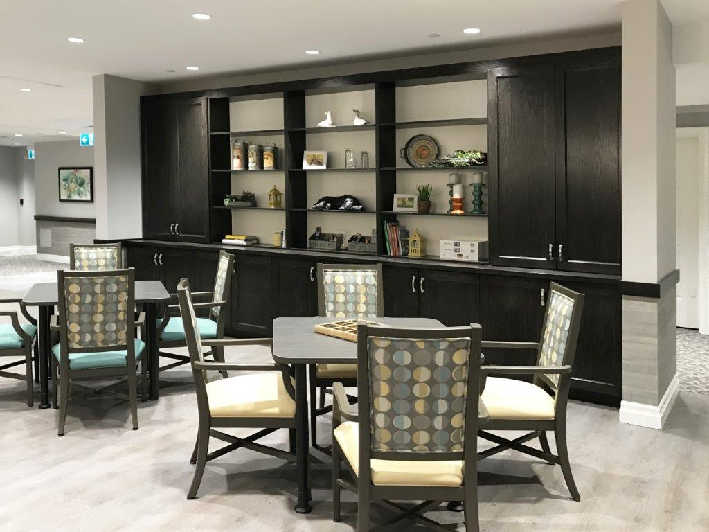 Dining area for retirement home with black built in bookshelves.