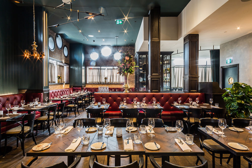 Restaurant area at the Broadview Hotel with red tufted leather seating and pendant lamps.