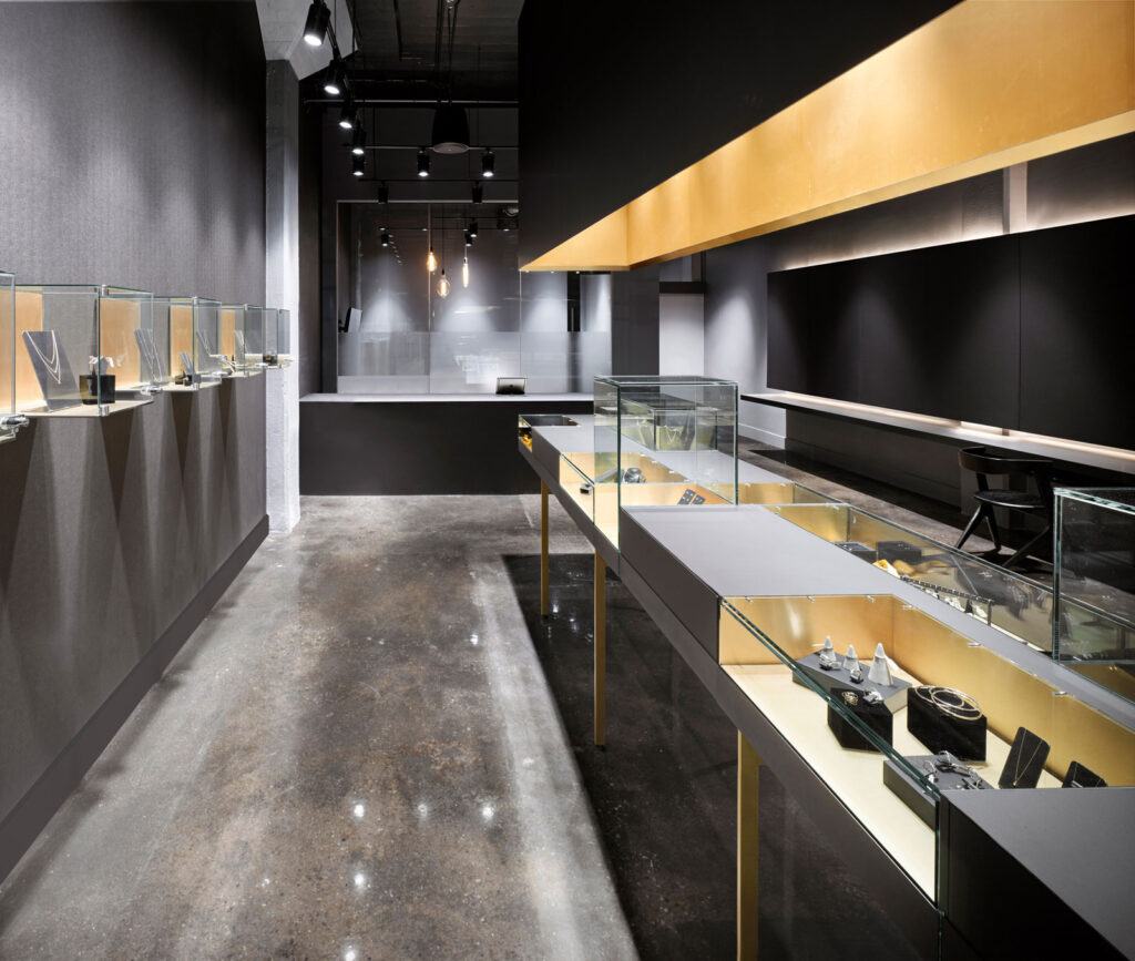 Sleek and modern jewellery store with polished concrete floors, gray walls and glass and gold display cases.