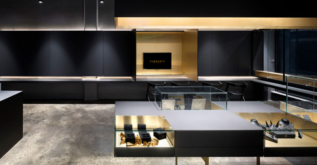 Jewellery cases in slate gray and gold shown in the open format with TV on display.