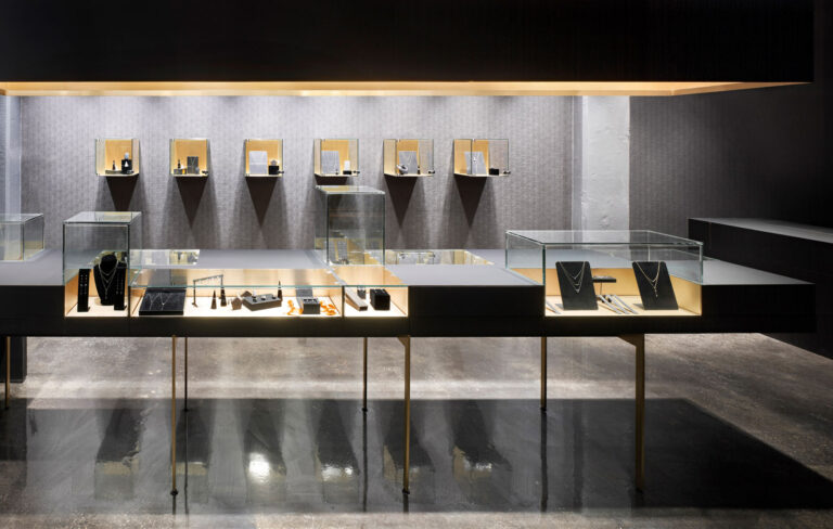 Jewellery displays featuring minimalist designs with a gold backdrop.