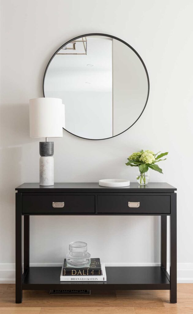 Black console table with a round mirror above.