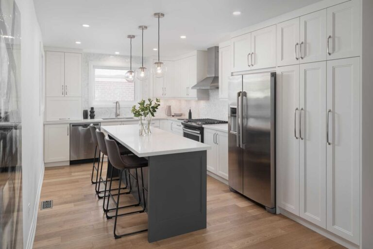 A modern white kitchen with hardwood floors and an 8 foot long island in the centre.