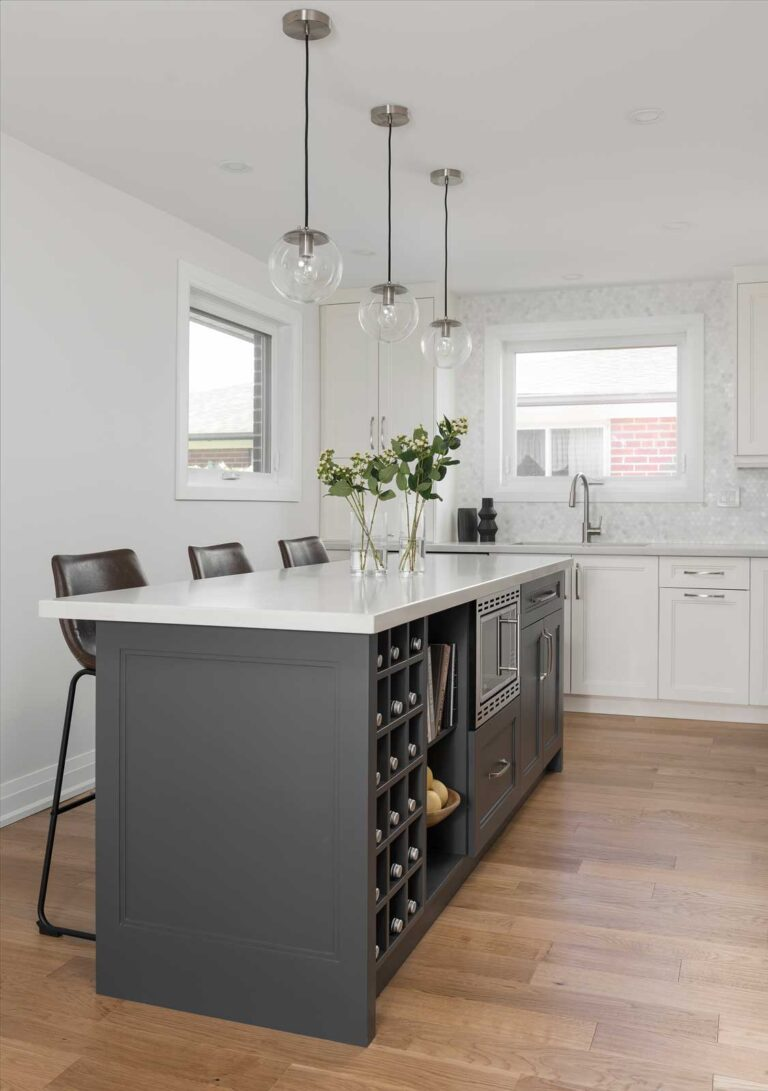Kitchen with white oak flooring, a dark gray island in the centre and a white marble top.
