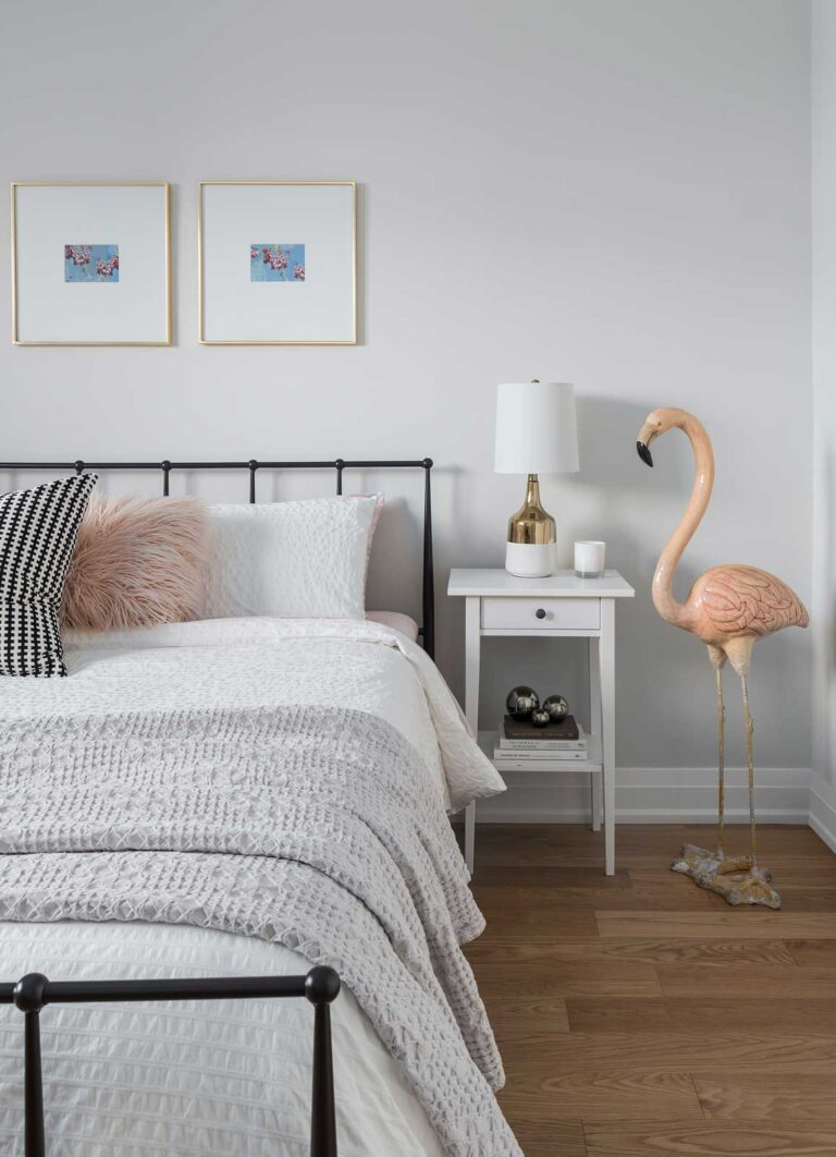 Crisp white bedroom with black iron bedstead and a flamingo sculpture.