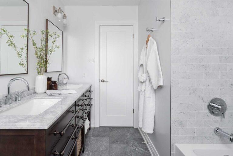 Sleek white bathroom with dark vanity with pale marble top.