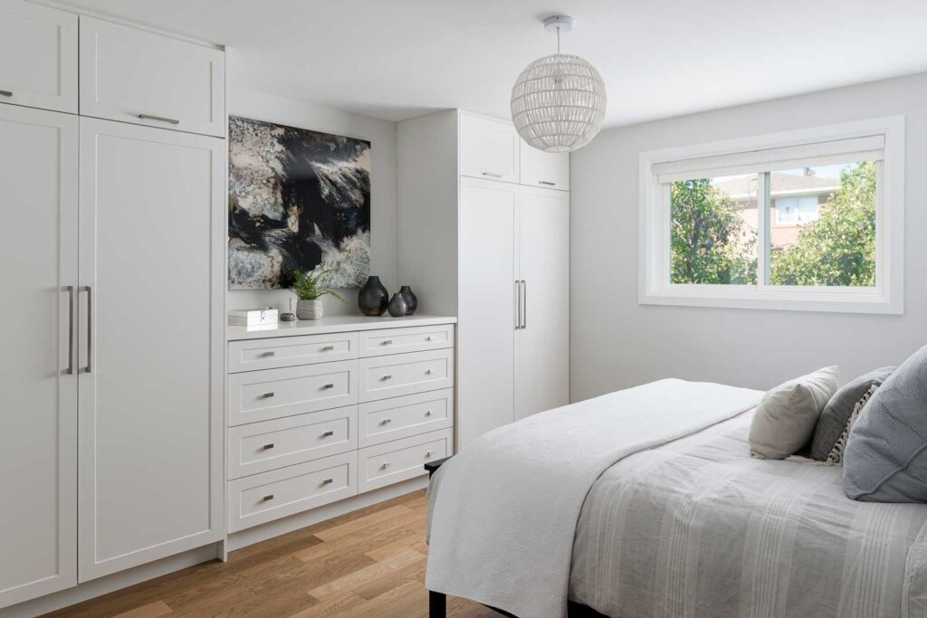 A serene modern bedroom with two white built-in closets and a bed made up with throw pillows.