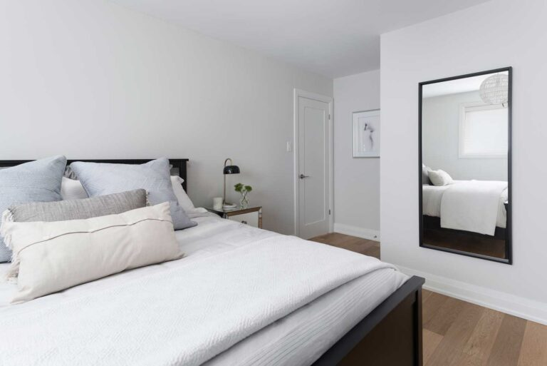 Calm white bedroom with white oak flooring and white sheets.