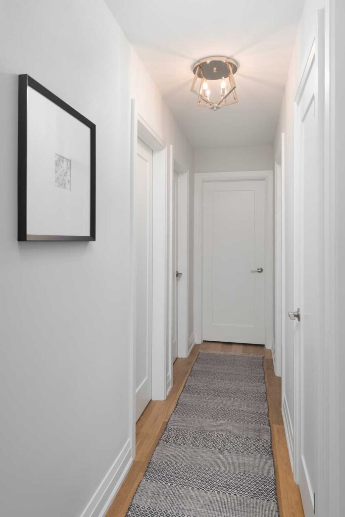 Hallway with white oak floors, pale gray walls and a geometric black and white carpet runner on floor.